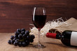 Red wine. Bottle and Wineglass with dark grapes branch. On rustic wooden background.