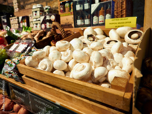 Poster White button mushrooms on a shelf at a farm shop, England, UK.