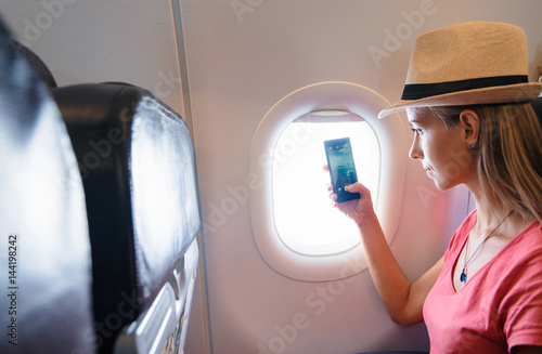 Woman using smart phone in aircraft.