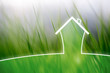 Concept artistic eco healthy living house on blurred meadow background.