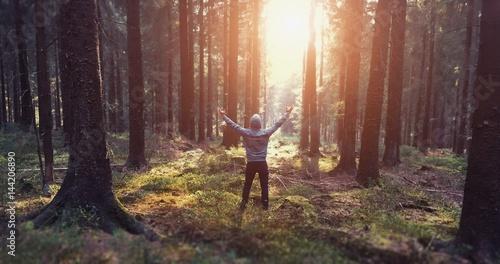 junger mann im wald bei sonnenaufgang