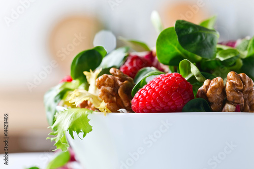 Green vegetarian salad with raspberry and walnut .