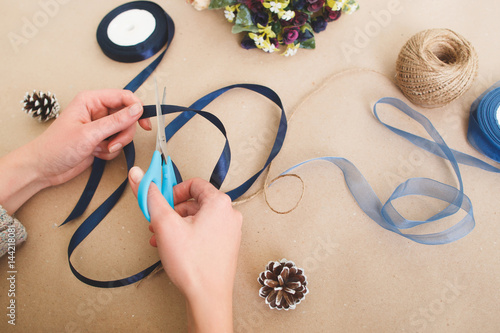 Unrecognizable woman make creative decorations from ribbons on beige background, top view Poster