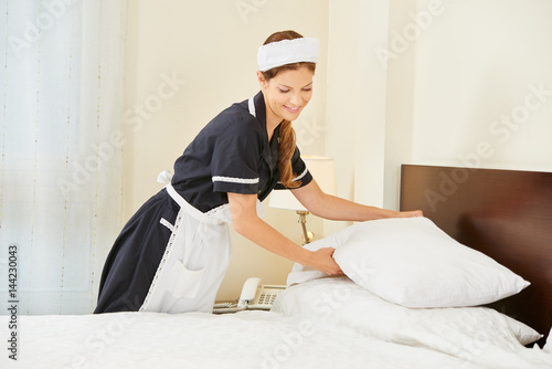 Hotel maid making bed in hotel room