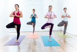 Portrait of group of people practicing yoga at home.