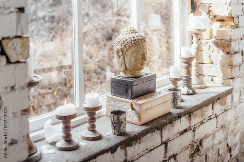 Decoration in boho style. Candles and sculpture of Buddha Poster