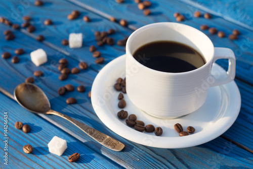 Coffee cup and beens on a table of blue boards