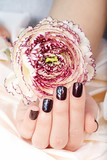 Hand with short manicured nails colored with dark purple nail polish with foil design and flower