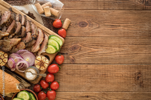 Sliced grilled meat barbecue on cutting board with vegetable and wine glass .