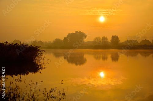 Poster Zamglony świt nad jeziorem i samotną wyspą.