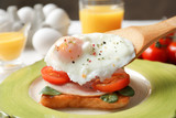 Putting poached egg onto sandwich. Cooking eggs Benedict