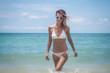 Beautiful young woman in a white bikini on a beautiful paradise sea beach