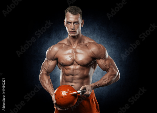 Handsome man with big muscles, posing at the camera in the gym - 144302274