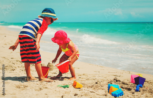 little boy and girl play with sand on summer beach Poster