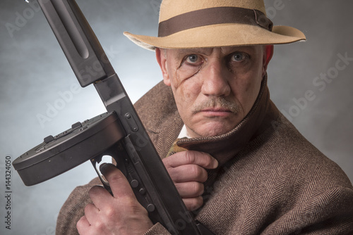 Poster 1940s male gangster holding a machine gun, on a grey smoky background