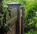 Alte Backsteinmauer um einen Garten, über die Wasser aus einem Gartenschlauch spritzt