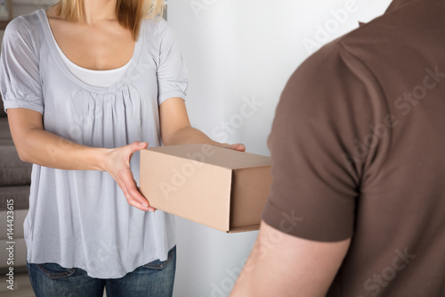 Woman Taking Box From Delivery Man Poster