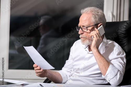 Bearded senior businessman talking on mobile phone, hard light Poster