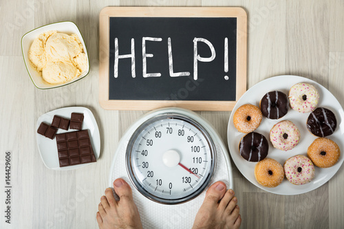 Man Measuring His Weight With Help Sign And Dessert