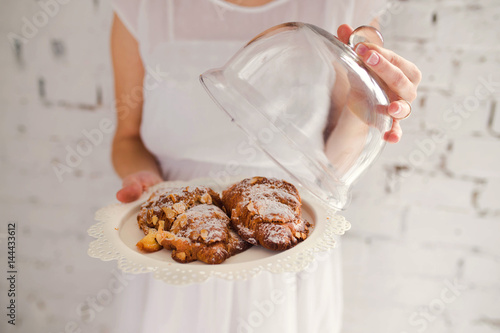 Plakat Girl in white dress holds a plate with croissants in hands