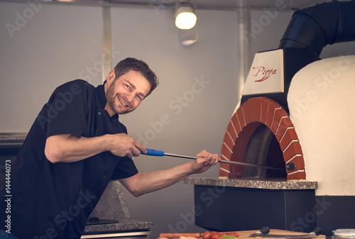 Foto op Canvas Pizzeria Chef einer Pizzeria mit Steinofen