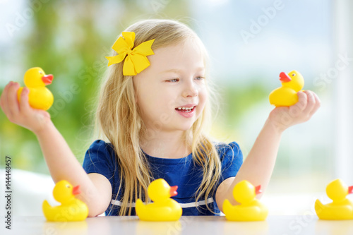 Cute little girl playing with rubber ducklings at home Poster
