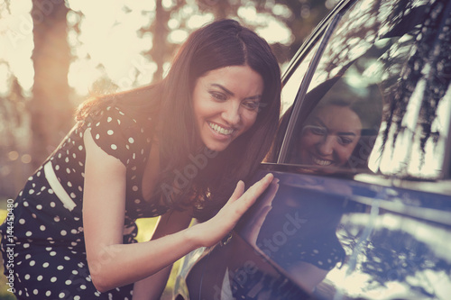 Excited woman and her new car with sunlit forest in background