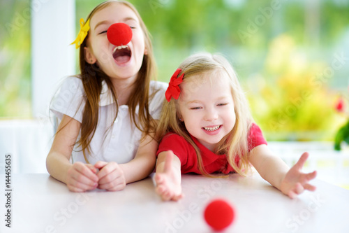 Happy little sisters wearing red clown noses having fun together on sunny summer Poster