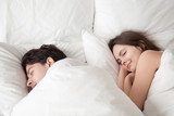 Fototapety Young woman and man lying asleep in cozy big white bed at home under blanket, soft sleep, couple sleeping together with smiles on their faces, lovers do not want to wake up in the morning
