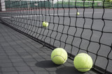 Tennis balls in front of net on court