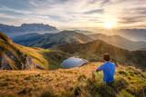 Man sitting on a mountain summit enjoying the view