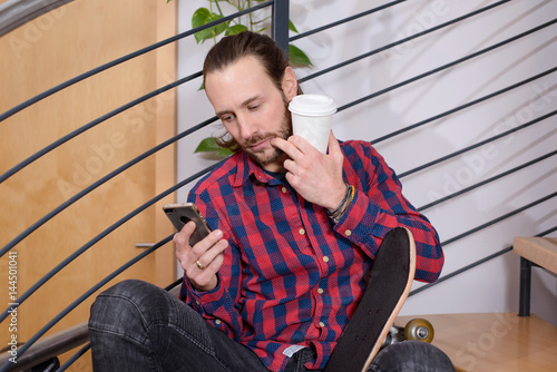 Poster young man sitting on stairs and using phone
