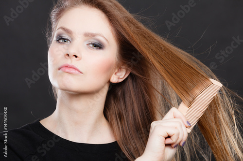 Poster Long haired woman combing her hair.