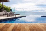 Fototapety Wood table top on Beach chair in outdoor with swimming pool and sea view andaman sea.