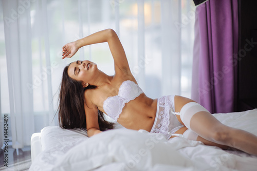 Plakát Beautiful bride in white lingerie showing sexy pose leaning at bed over her bedroom with flowers