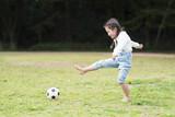 サッカーボールで遊ぶ裸足の女の子