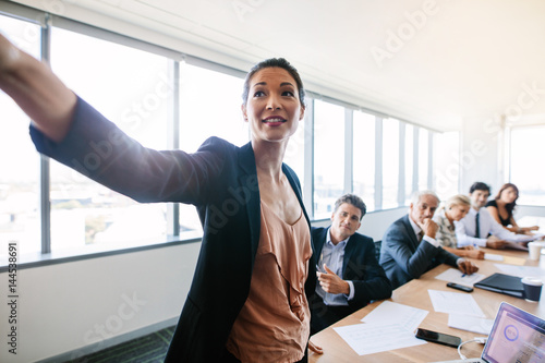 Asian businesswoman presenting her ideas to colleagues Poster