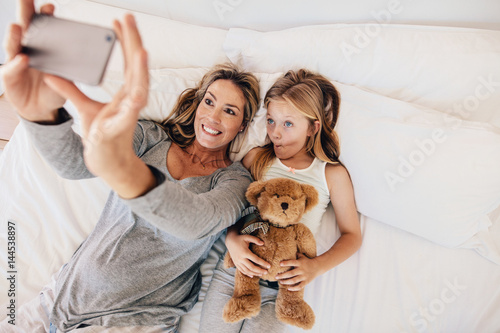 Plagát Mother and daughter lying on bed and taking selfie