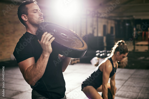 Young sportsmen having workout with weight disks - 144539416