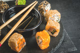 Concept of Japanese food: sticks and sushi, soy sauce and pickled ginger on a black slate stone table. Top view copy space