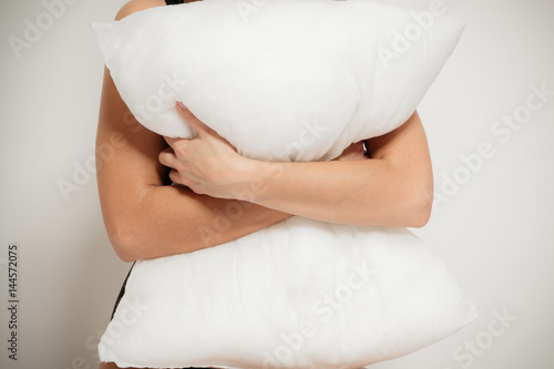 Closeup of white pillow in arms in the bedroom