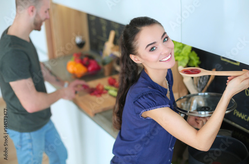 Couple cooking together in their kitchen at home - 144573477