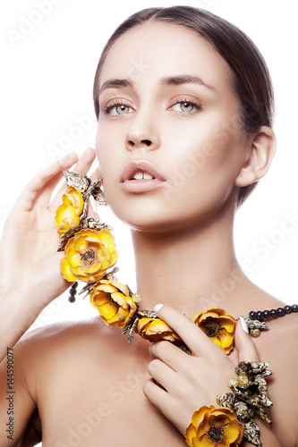 Poster Beauty portrait of attractive caucasian young girl with natural make-up and yellow flowers necklace looking at camera