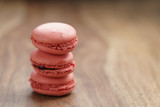 closeup shot stack of pastel colored macarons with strawberry flavour on wood table, copy space