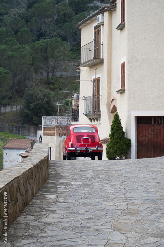 Red colored Classic car cruising on the road Poster