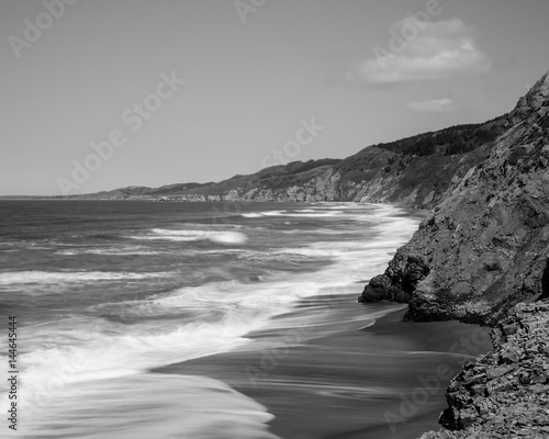 Black and white rendering a view of the Pacific Coast from Point Reyes National Seashore, Marin County, California, USA, near Alamere Falls, during the high tide - 144645444