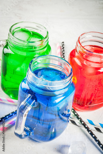 Bright colorful summer drinks with ice. Sweet water in mason jar - blue, red and green. On a white table with multicolored straws, copy space