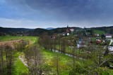 Srbska Kamenice, Czech republic - April 08, 2017: river Kamenice flowing through village with a church on hill in spring  natural reserve Arba in tourist area Labske piskovce at evening