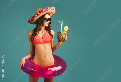 young sexy woman in bikini and sombrero with swim ring, tropical cocktail isolat Poster