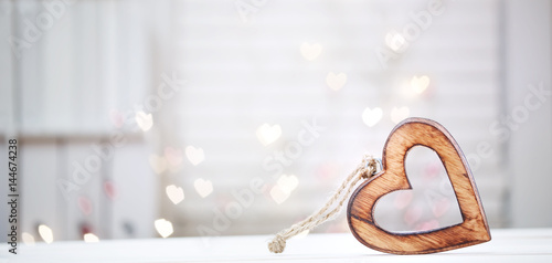 Wooden heart on abstract light background